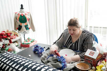 """Doris Cochran works on """"an ugly sweater,"""" which she is planning to sell, Jan. 18, 2019 in her apartment in Arlington, Va.,"""