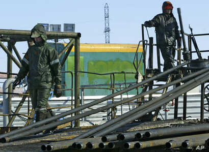 FILE - Oil workers prepare to pump water into the Priobskoye oil field in Western Siberia, which once belonged to the Yukos oil company and were bought by state oil company Rosneft, after a controversial auction in 2004. On the building in the backgr...