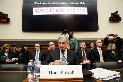The national debt is shown behind Federal Reserve Chairman Jerome Powell as arrives to testify on the semiannual monetary policy report to the House Financial Services Committee, Tuesday, Feb. 27, 2018, in Washington.