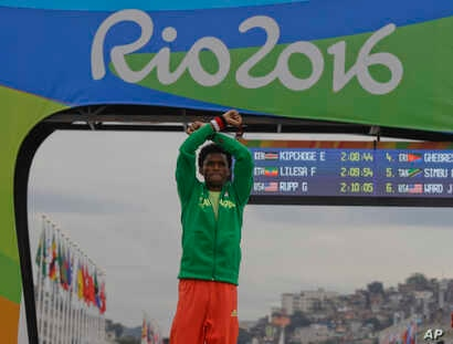 Silver medalist Ethiopia's Feyisa Lilesa, crosses his arms as he celebrates on the podium after the men's marathon at the 2016 Summer Olympics in Rio de Janeiro, Brazil, Sunday, Aug. 21, 2016.