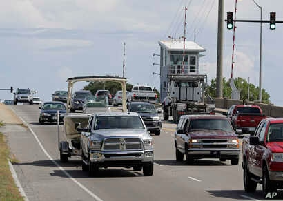 People drive over a drawbridge in Wrightsville Beach, N.C., as they evacuate the area in advance of Hurricane Florence, Sept. 11, 2018.