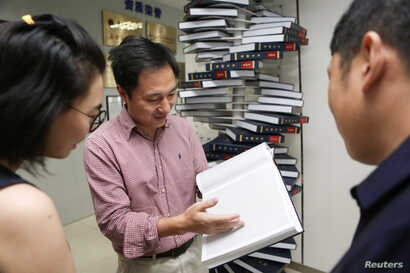 """FILE - Scientist He Jiankui shows """"The Human Genome"""", a book he edited, at his company Direct Genomics in Shenzhen, Guangdong province, China, Aug. 4, 2016."""