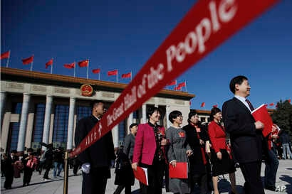 A soldier in usher uniform stands guard as delegates leave the Great Hall of the People after the closing session of China's National People's Congress (NPC) in Beijing, March 15, 2019.