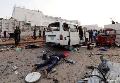 The dead body of an unidentified man is seen at the scene of an explosion in Mogadishu, Somalia, Nov. 9, 2018.