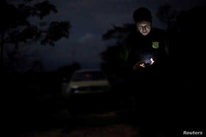An agent of the Brazilian Institute for the Environment and Renewable Natural Resources, or Ibama, looks at a GPS device during an operation to combat illegal mining and logging, in the municipality of Novo Progresso, Para State, northern Brazil, Nov...