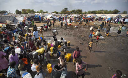 FILE - Displaced people gather around a water truck to fill containers at a United Nations compound which has become home to thousands of people displaced by the recent fighting, in the capital Juba, South Sudan, Dec. 29, 2013.