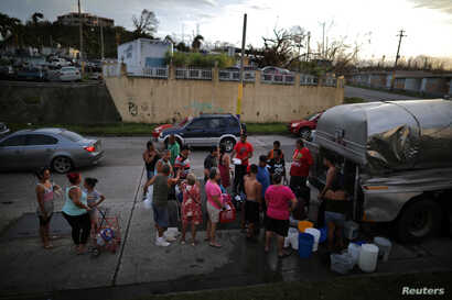 Local residents wait in line during a water distribution in Bayamon following damages caused by Hurricane Maria in Las Piedras, Puerto Rico, Oct. 1, 2017