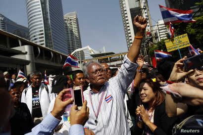 Protest leader Suthep Thaugsuban greets the crowd as he leads anti-government protesters marching through Bangkok's financial district, Jan. 21, 2014.
