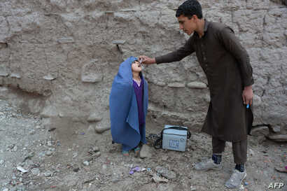 An Afghan health worker administers the polio vaccine to a child during a vaccination campaign on the outskirts of Jalalabad on March 12, 2018.