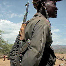 An armed pastoralist watches over his herd with his rifle - the weapon of choice among herders - slung over his shoulder, Aug 2010