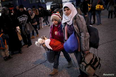 A Syrian girl carries her dolls as refugees and migrants arrive aboard a passenger ferry at the port of Piraeus, near Athens, Greece, Jan. 13, 2016.