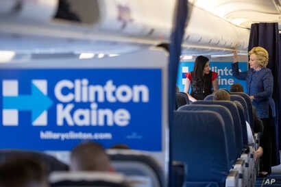 Democratic presidential candidate Hillary Clinton speaks with senior aide Huma Abedin (L) aboard her campaign plane at Westchester County Airport in White Plains, New York, Oct. 28, 2016. The FBI found the potentially incriminating emails on a comput...