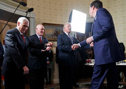 FILE - Vice President Mike Pence, left, and Secret Service Director Joseph Clancy stand as President Donald Trump shakes hands with FBI Director James Comey during a reception for inaugural law enforcement officers and first responders in the Blue Ro...