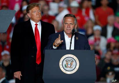 President Donald Trump listens as Rep. Mike Bost, R-Ill., speaks during a rally at Southern Illinois Airport,  Oct. 27, 2018, in Murphysboro, Ill.
