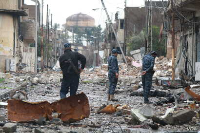 7080: Iraqi Federal police tour a neighborhood shortly after a battle, still littered with rubble and bodies of militants in Mosul, Iraq on March 16, 2017.