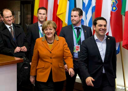 Greek Prime Minister Alexis Tsipras, right, walks with German Chancellor Angela Merkel, center, as they leave an EU summit in Brussels, March 8, 2016.