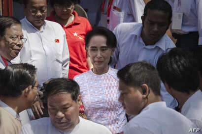 Myanmar opposition leader Aung San Suu Kyi (C) leaves the headquarters of the National League of Democracy (NLD) after she made a speech to a small crowd and the media in Yangon on Nov. 9, 2015.