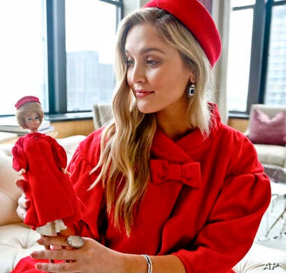 In this Nov. 5, 2018 photo, model Kelsey Elliott holds a Barbie doll while wearing a matching outfit from designer Katie Echeverry in New York.