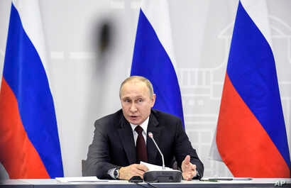Russian President Vladimir Putin gestures while speaking at the Forum of Small Towns and Historical Settlements in Kolomna, about 100 kilometers (62.5 miles) south of Moscow,  Jan. 17, 2018.