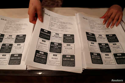 A staff member prepares leaflets of election campaign pledges before a news conference by  Tokyo Governor Yuriko Koike, head of Japan's Party of Hope, for it's unveiling in Tokyo, October 6, 2017.