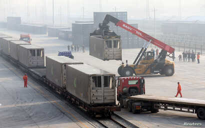 Workers unload containers from a train at Dahongmen Railway Station, Beijing, Jan. 14, 2019.