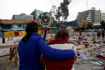 Residents pray for victims at a makeshift altar, in an area that used to be a textile factory before it was destroyed in an earthquake, in Mexico City, Sept. 24, 2017.