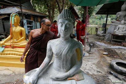 Jeremy, a Buddhist monk from Australia, inspects a Buddha statue at a workshop at the rehabilitation and detox area at Wat Thamkrabok monastery in Saraburi province, Thailand.
