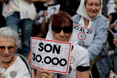 """FILE - Mothers of """"Plaza de Mayo"""" member Tati Almeida holds a sign that reads in Spanish """"They are 30,000,"""" referring to those killed by the Argentine dictatorship, as she listens to the verdicts for the accused in a human rights trial, Nov. 29, 2017..."""