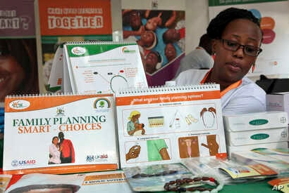 FILE - Health worker Sylvia Marettah Katende displays reproductive health products and information at a family planning exhibition in Kampala, Uganda, Sept. 26, 2017.