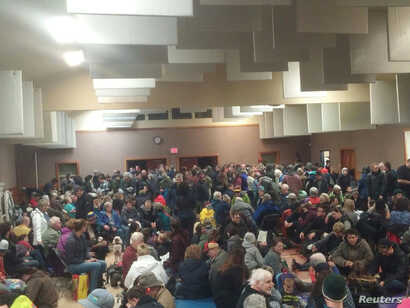 People are seen waiting at the Tofino Community Hall during a tsunami warning, in British Columbia, Canada, Jan. 23, 2018, in this image obtained from social media.