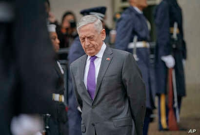 FILE - Defense Secretary Jim Mattis waits for Chinese Minister of Defense General Wei Fenghe to begin an arrival ceremony at the Pentagon, Nov. 9, 2018.