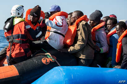 A group of 47 migrants is helped by a Sea-Watch 3 crew member, left, during their transfer from a rescued inflatable boat onto a Sea-Watch 3 RHIB (Rigid Hull Inflatable Boat) during a rescue operation by the Sea-Watch 3 off Libya's coasts, Jan. 19, 2...