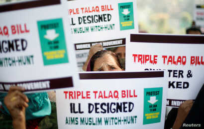 """FILE - Muslim women hold placards during a protest against a bill passed by India's lower house of Parliament last week that aims at prosecuting Muslim men who divorce their wives through the """"triple talaq,"""" or instant divorce, in New Delhi, Jan. 4, ..."""