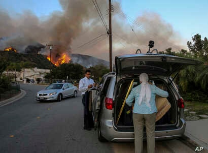 Residents evacuate their home as a wildfire is burning along a hillside in Duarte, California, June 20, 2016.