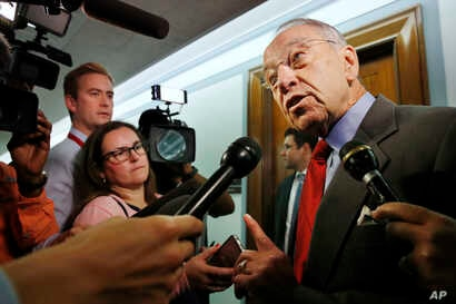 Sen. Chuck Grassley, R-Iowa, right, answers questions from reporters about allegations of sexual misconduct against Supreme Court nominee Brett Kavanaugh as he arrives for a Senate Finance Committee hearing on Capitol Hill in Washington, Sept. 26, 20...