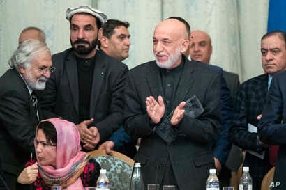 Former Afghan President Hamid Karzai, second from right, applauds during the talks in Moscow, Feb. 6, 2019. The Taliban has so far refused to negotiate with the government of President Ashraf Ghani.
