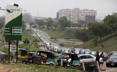 Cars queue to buy fuel at a petrol station in Abuja, Nigeria, Friday, April 1, 2016.