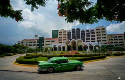 FILE - A vintage car passes in front of the Four Points by Sheraton hotel in Havana, Cuba, June 28, 2016. American hotel giant Starwood has begun managing this hotel owned by the Cuban military.