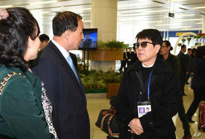 South Korean singer Cho Yong-pil, right, talks with North Koreans at the Pyongyang Airport in Pyongyang, North Korea, March 31, 2018.