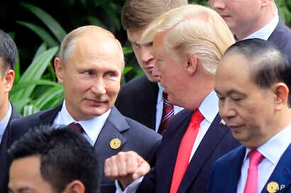 FILE - Russian President Vladimir Putin (L) and U.S. President Donald Trump talk as they arrive for the family photo session during the Asia-Pacific Economic Cooperation (APEC) Summit in Danang, Vietnam, Nov. 11, 2017.