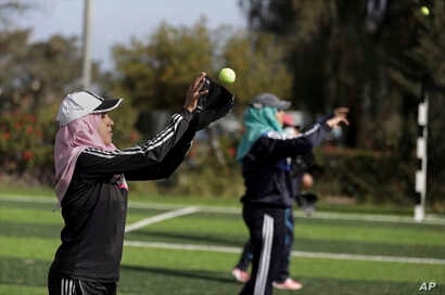 Palestinian women practice with tennis balls while training for an all-women's baseball game on a soccer field in Khan Younis, southern Gaza Strip, March 19, 2017.