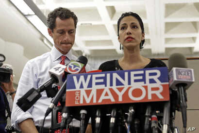 Anthony Weiner, left, listens as his now estranged wife, Huma Abedin, speaks during a news conference during his mayoral campaign in New York, July 23, 2013. Abedin is one of Hillary Clinton's top aides.