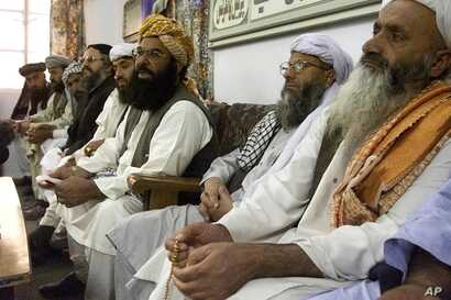 FILE - Abdul Ghafoor Haidari, third from right, secretary general of the Pakistani religious party Jamiat Ulema-e-Islam, addresses a news conference with his party members in Quetta, Pakistan, Oct 14, 2001.