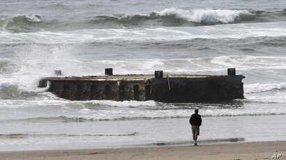 FILE - A man looks at a 70-foot-long dock with Japanese lettering that washed ashore on Agate Beach in Newport, Ore., June 6, 2012,