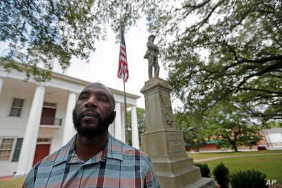 In this Aug. 1, 2018 photo, Ronnie Anderson, an African-American man charged with possession of a firearm by a convicted felon, poses in front of a confederate statue on the lawn of the East Feliciana Parish Courthouse.