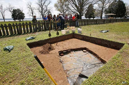 Historic Jamestown staff archaeologist Bruce McRubert, left, and Lee McBee, right, dig and inform visitors at the dig site of the Angelo slave house in Jamestown, Va., April 10, 2018.