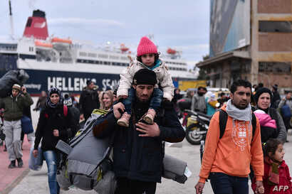 Hundreds of migrants and refugees walk at the port of Piraeus upon their arrival from the island of Lesbos, Feb. 10, 2016. EU migration commissioner Dimitris Avramopoulos urged member states to accelerate the relocation of refugees from overstretched...