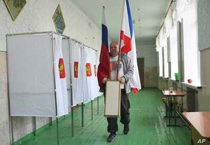 A polling station official with Russian national and Crimea flags is prepared for the 2018 Russian presidential election, in Simferopol, Crimea, March 17, 2018.