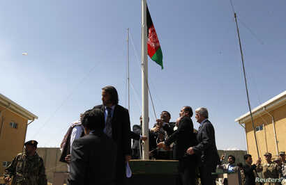 Afghan officials raise their national flag during a ceremony to hand over the Bagram prison to Afghan authorities, at the U.S airbase in Bagram, north of Kabul, September 10, 2012.