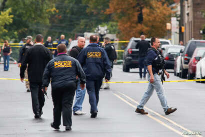 Police officers walk near the site where Ahmad Khan Rahami, sought in connection with a bombing in New York, was taken into custody in Linden, New Jersey, U.S., Sept. 19, 2016.